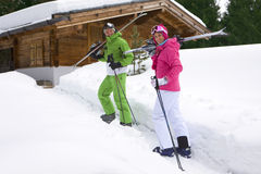 Couple standing in snow near lodge with skis Royalty Free Stock Image
