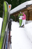 Couple standing in snow near lodge with skis looking at mail stock image