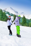 Couple standing on snowboards holding hands Royalty Free Stock Photo