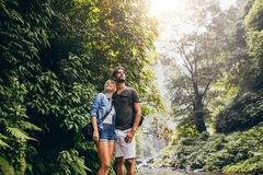 Couple standing by stream in woods Stock Image