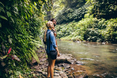 Couple standing by stream in woods. Outdoor shot of couple of tourist standing by a small stream in the rainforest. Hiker couple standing by stream in woods Royalty Free Stock Photography
