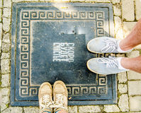 A couple standing in the street, top view on feet. Two pairs of sneakers blue and beige with laces and bows on the manhole with text saying `the happiness will Royalty Free Stock Photography