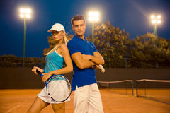 Couple standing at tennis court outdoors Stock Images