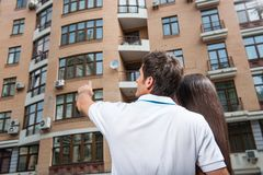 Couple standing with their backs towards camera. Man pointing to apartment window for brunette woman stock photos
