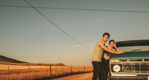 Couple enjoying a road trip. Couple standing beside their car on a highway in country side. Man and women on a road trip Royalty Free Stock Photography