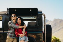Couple by their car admiring a view. Couple standing beside their car on a highway. Man embracing his women while standing outdoors and looking away smiling royalty free stock photo