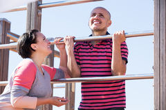 Couple standing to wall bars Royalty Free Stock Photography