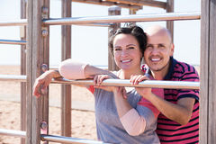 Couple standing to wall bars Stock Images