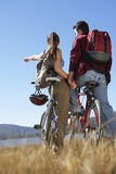 Couple Standing Together With Bicycles BY Lake Stock Image