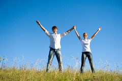 Couple standing together with hands up Royalty Free Stock Photos