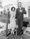 Couple standing together with one oversized baseball bat Stock Images