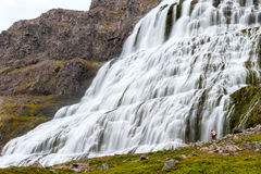 Couple standing under majestic cascade waterfall Dynjandi, Iceland royalty free stock photo