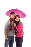Couple standing underneath an umbrella Stock Images