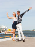 Couple standing and waving in port Stock Images