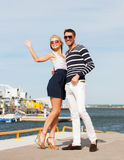 Couple standing and waving in port Stock Photos