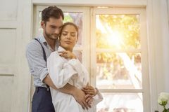 Couple standing by the window. In the morning Royalty Free Stock Photo