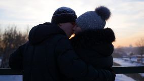 The couple stands on a bridge and kiss at sunset. Winter time stock video