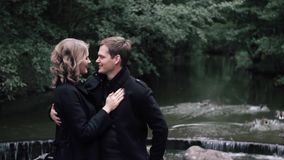 The couple stands on a bridge in the Park, birds flying in the background, Slow motion. Couple in love stands on a bridge in the Park, birds flying in the stock video