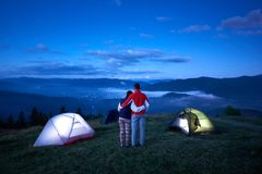 Couple stands with their backs to camera embracing each other enjoying the dawn in mountains. Couple stands near camping with their backs to camera embracing royalty free stock photos
