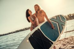 Couple standup paddle boarding. Beautiful young couple is hugging and smiling while resting on the beach, guy is carrying a paddle board Royalty Free Stock Image