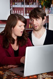 Couple staring in disbelief at a computer laptop. Woman and man staring in disbelief at a laptop Royalty Free Stock Photo