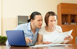 Couple staring financial documents at table in home Royalty Free Stock Photo