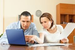 Couple staring financial documents at table Royalty Free Stock Photos