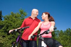 Couple Staring Happily - horizontal. A young, attractive couple sits on a pair of bikes, on a sunny day, at a park, staring happily at each other. - horizontally Royalty Free Stock Photography
