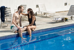 Couple Staring by Pool - horizontal. A young couple, with their feet dangling into the water, stare at each other lovingly. - horizontally framed royalty free stock images