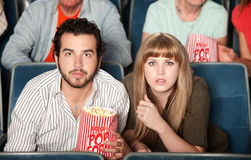 Couple Staring in Theater. Couple with popcorn bag staring ahead in a theater Stock Photo
