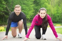 Couple in starting position. Young sport couple in starting position prepared to compete and run Royalty Free Stock Photography