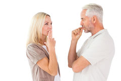 Couple staying silent with fingers on lips Royalty Free Stock Photos