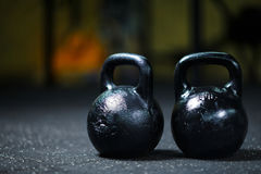 A couple of steel black kettlebells on a blurred background. A kettlebell on a gym floor. Workout. Copy space. Royalty Free Stock Image