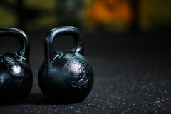 A couple of steel black kettlebells on a blurred background. A kettlebell on a gym floor. Workout. Copy space. Royalty Free Stock Photography