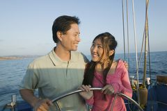 Couple at steering wheel of sailboat Stock Image
