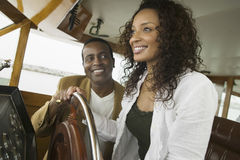 Couple At Steering Wheel Of Yacht Stock Image