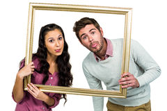 Couple sticking out tongue while holding picture frame. On white background Royalty Free Stock Images