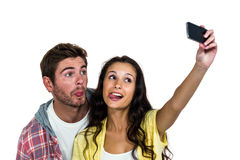 Couple sticking out tongue while taking selfie. On white screen Royalty Free Stock Photos