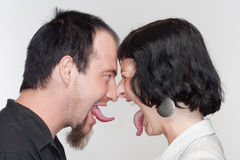 Couple sticking out tongues. Couple sticking out their tongues at each other - on white Stock Images