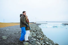 Couple at Stone Lake Shore in Iceland Royalty Free Stock Photos
