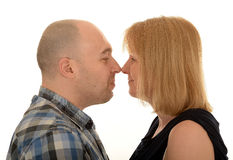 Couple stood nose to nose. Portrait of a happy middle aged couple stood with their noses together, white studio background Royalty Free Stock Photos