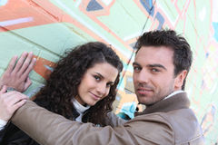 Couple stood by wall. Attractive couple stood in front of graffiti-ed wall Royalty Free Stock Image