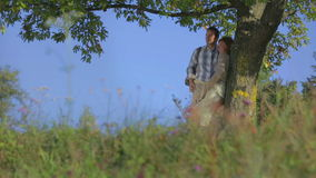 Couple stops under the tree stock footage