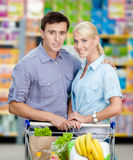 Couple in the store with cart full of food Stock Photography
