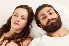 Couple strained relations. Lying on bed with sad expression Stock Photography