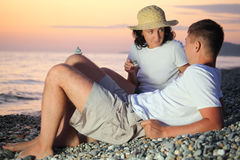 Couple in straw hat design pyramids from pebble Stock Image