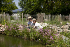 Couple with a straw hat on the garden pond. Picking pink flowers and watch the water Royalty Free Stock Images