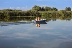 Couple with Straw Hats on a Small Motor Boat in the River royalty free stock photo