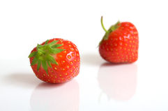 Couple strawberries. Two strawberries on a white surface Stock Image