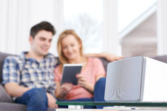 Couple Streaming Music From Digital Tablet To Wireless Speaker Royalty Free Stock Image